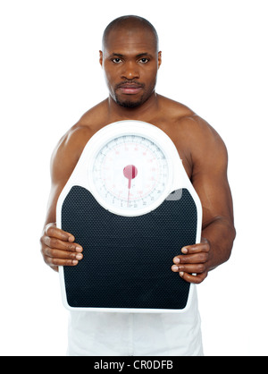 Attractive athlete showing weighing scale against white background - Stock Photo