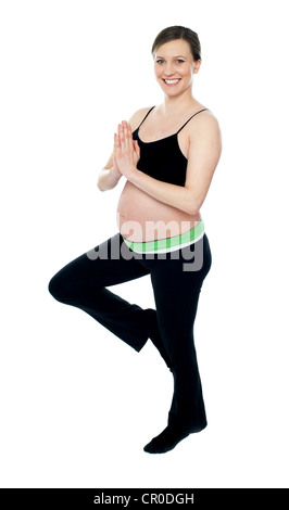 Portrait of beautiful pregnant woman doing yoga. Standing on one leg isolated against white background - Stock Photo