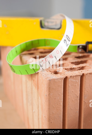 Spirit level and a measuring tape on a brick - Stock Photo