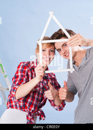 Young couple holding a folding carpenter's ruler in the shape of a house - Stock Photo