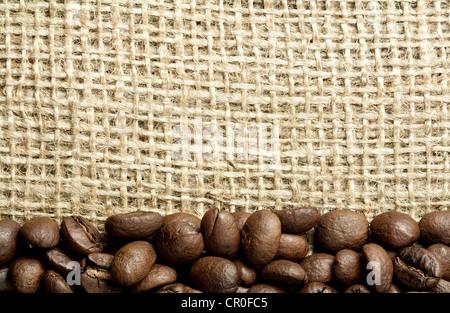 heap of coffee beans on burlap - Stock Photo