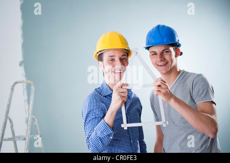 Two young tradesmen holding a folding carpenter's ruler in the shape of a house - Stock Photo