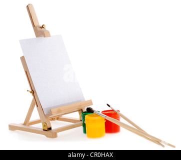 Three gouache paints, three small brushes and an easel. - Stock Photo