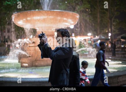 A man aims his camera to take a picture near the fountain in Bryant Park in New York City. - Stock Photo