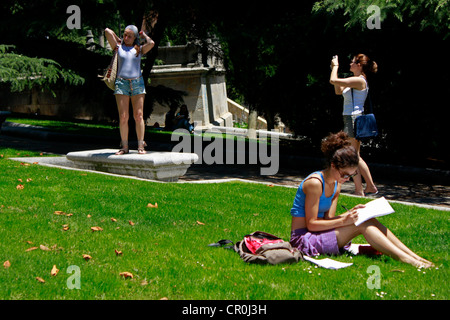 A student reads sitting on the grass as two female tourists take pictures in a park of Salamanca, Castilla y Leon, - Stock Photo