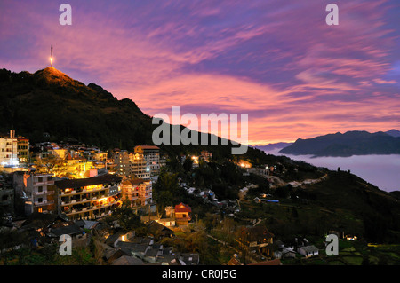 Lit houses, Sapa with Mt. Ham Rong and transmission tower, spectacular cloud mood, sea of clouds at sunset, Muong - Stock Photo