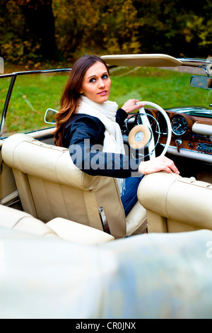 Young woman in front of post-war classic car - Stock Photo