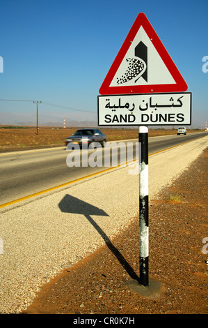 Road sign in English and Arabic warning of shifting sand dunes at a desert road, Sultanate of Oman, Middle East, - Stock Photo