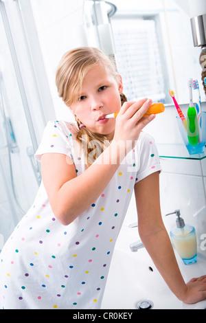 Little girl brushing her teeth in the bathroom - Stock Photo
