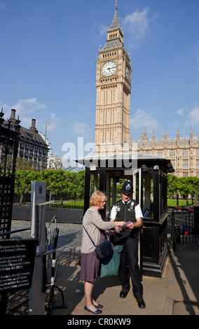 A policeman gives information to a female tourist, House of Parliament, London, England, UK - Stock Photo