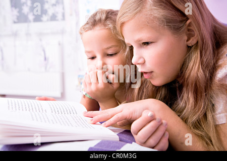 Two girls, sisters reading in bed - Stock Photo