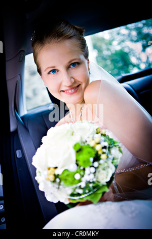 Young bride in the car - Stock Photo