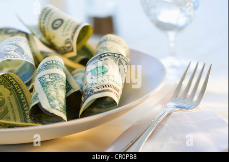 Paper currency on dinner plate, studio shot - Stock Photo