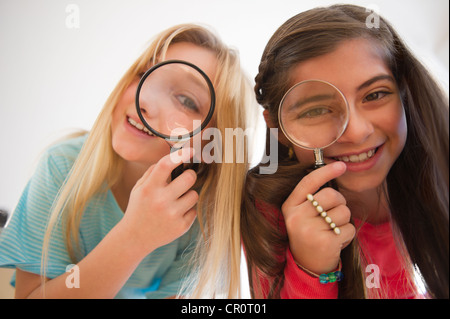 USA, New Jersey, Jersey City,  Two girls looking through magnifying glasses - Stock Photo