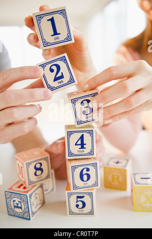 USA, New Jersey, Jersey City, Close up of man's and woman's hands arranging blocks with numbers - Stock Photo