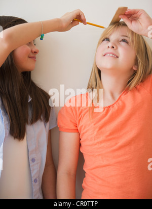 USA, New Jersey, Jersey City, Two girls measuring height - Stock Photo