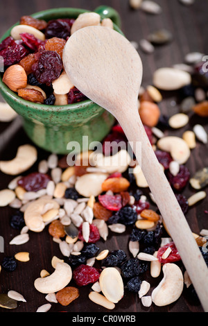 Various nuts, kernels, dried fruits, and a wooden spoon - Stock Photo