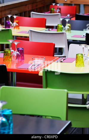 colored tables and chairs on a restaurant terrrace - Stock Photo