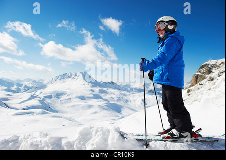 Boy in skis on snowy mountaintop - Stock Photo