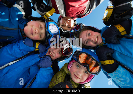 Children in ski gear standing together - Stock Photo