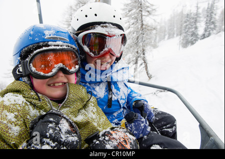 Snow-covered children in ski lift - Stock Photo