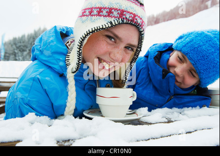 Girl drinking hot chocolate in snow - Stock Photo