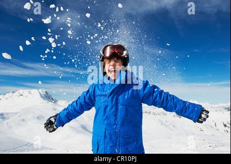 Boy cheering on snowy mountaintop - Stock Photo