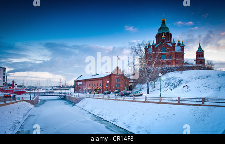Snow-covered castle by frozen river - Stock Photo