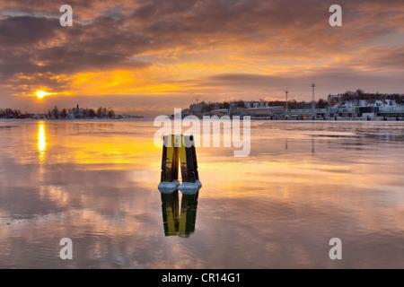 Sun setting over urban pier - Stock Photo