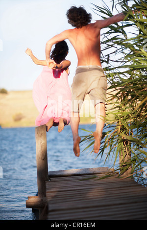Couple jumping off dock into lake - Stock Photo