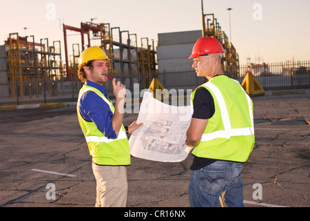 Construction workers reading blueprint - Stock Photo