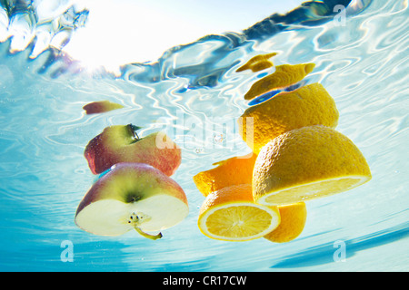 Fruit floating in swimming pool - Stock Photo