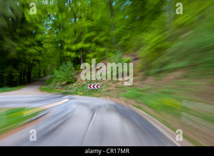 High speed motion, country road in a wooded area with a sharp left turn, Germany, Europe, PublicGround - Stock Photo