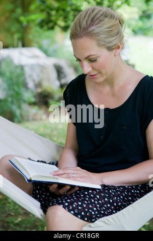Woman reading book in hammock - Stock Photo