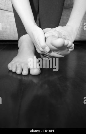 A young woman rubs her aching feet on the sofa. - Stock Photo