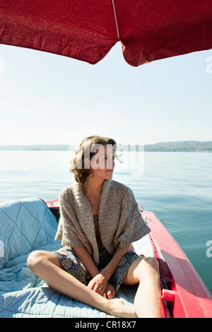 Woman relaxing in boat on still lake - Stock Photo