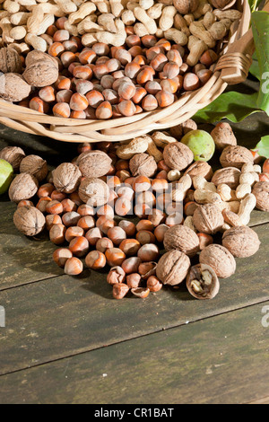 Wicker basket with mixed nuts, Walnuts (Juglans regia), Peanuts (Arachis hypogaea) and Hazelnuts (Corylus avellana) - Stock Photo