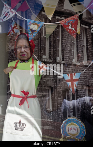A shop window in Lancaster with display of Queen Elizabeth II and reflection of street during Diamond Jubilee June - Stock Photo