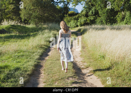 Teenage girl walking on dirt path - Stock Photo