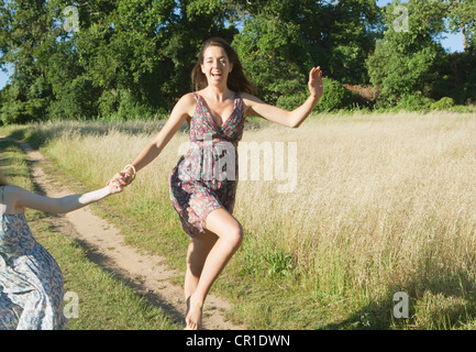 Teenage girls skipping on dirt path - Stock Photo