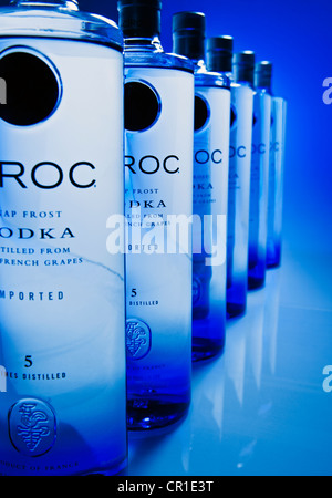 Ciroc Vodka bottles line up in perspective with a blue background - Stock Photo