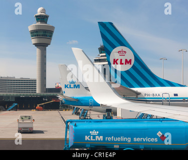 Amsterdam Schiphol Airport Air Traffic Control Tower with Royal KLM planes refueling at gate. Retro style colors - Stock Photo