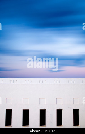 Moving clouds over a building. Long exposure shot. - Stock Photo