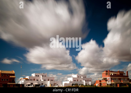 Moving clouds over buildings. Long exposure shot. - Stock Photo