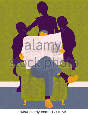 Family standing behind man reading newspaper in armchair - Stock Photo