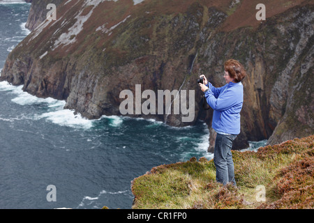 Woman taking pictures with a digital compact camera, at the cliffs of Slieve League, County Donegal, Ireland, Europe - Stock Photo