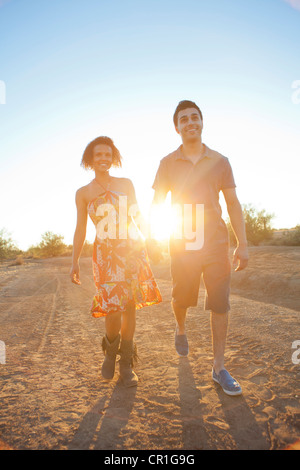 Couple walking together in desert - Stock Photo