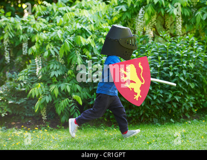 Boy playing with sword in backyard - Stock Photo