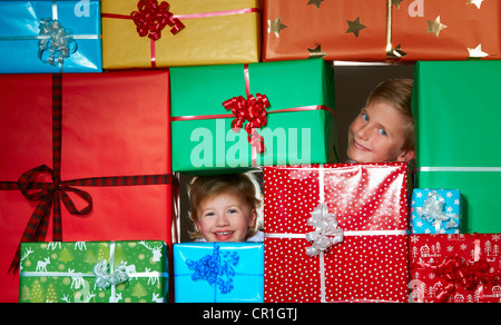 Children smiling in Christmas gift fort - Stock Photo