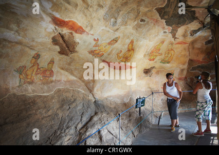 Tourists taking photos of ancient frescoes, Sigiriya (UNESCO World Heritage Site), North Central Province, Sri Lanka - Stock Photo